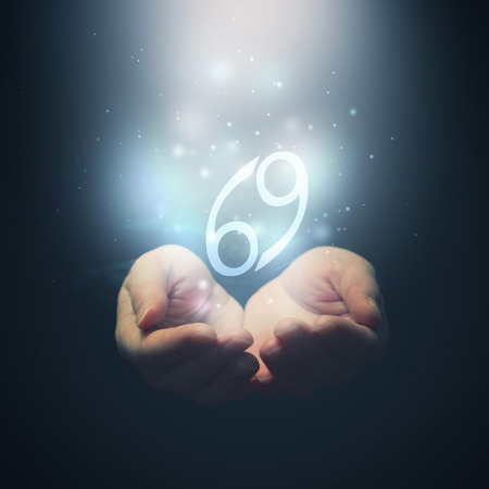 foretelling: Female hands opening to light and holding zodiac sign for Cancer  Horoscope symbols  Selective focus  Stock Photo