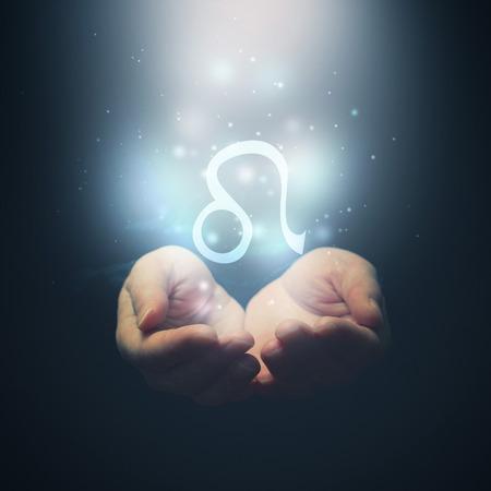 horoscope: Female hands opening to light and holding zodiac sign for Leo  Horoscope symbols  Selective focus  Stock Photo