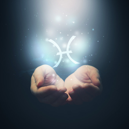 foretelling: Female hands opening to light and holding zodiac sign for Pisces  Horoscope symbols  Selective focus