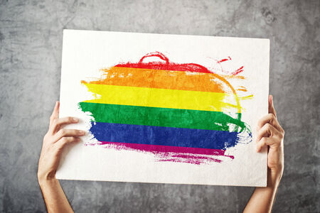 bisexual: Gay flag. Man holding banner with LGBT Flag. Supporting national team, patriotism concept. Stock Photo
