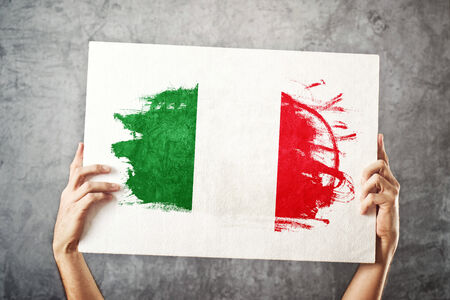 flaga włoch: Flaga Włochy. Mężczyzna trzyma transparent z włoskiej flagi. Wspieranie drużyny narodowej, patriotyzm pojęcie.