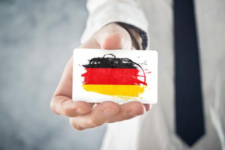 deutschland fahne: Deutsch Businessman holding Visitenkarte mit Deutschland-Flaggen-Internationale Zusammenarbeit, Investitionen, Gesch�ftsm�glichkeiten Konzept Lizenzfreie Bilder