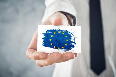 欧州連合旗国際協力、投資、ビジネス機会概念のビジネス カードを持っているヨーロッパの実業家