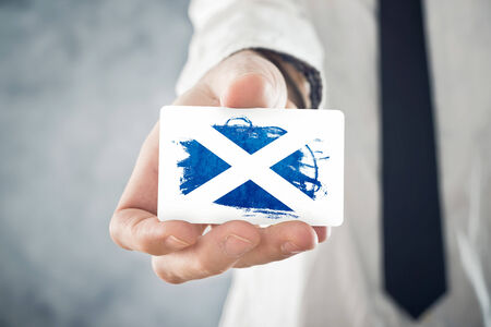 scotish: Scotish Businessman holding business card with Scotland Flag  International cooperation, investments, business opportunities concept  Stock Photo