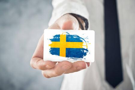 schweden flagge: Schwedischen Gesch�ftsmann h�lt Visitenkarte mit Schweden-Flagge Internationale Zusammenarbeit, Investitionen, Gesch�ftsm�glichkeiten Konzept
