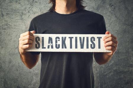 slacker: Man holding white banner with SLACTIVIST title, conceptual image Stock Photo