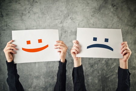 Happy and sad face. Women holding papers with happy and sad emoticons. Standard-Bild