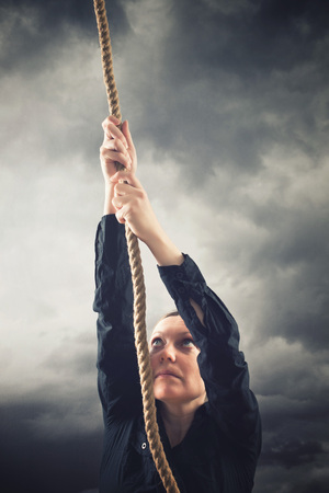 Woman climbing up with rope. Overcaming problems, obstacles and difficulties in life metaphor. photo