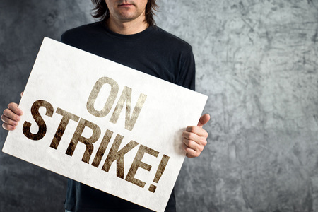 Man holding banner with ON STRIKE printed protest message  photo