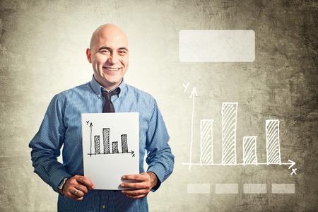 desarrollo económico: El hombre de negocios que sostiene el papel con el dibujo gráfico de barras. Situación de asunto.