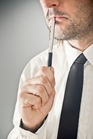 acknowledge: Businessman thinking with pencil in his mouth  Portrait of thoughtful business person