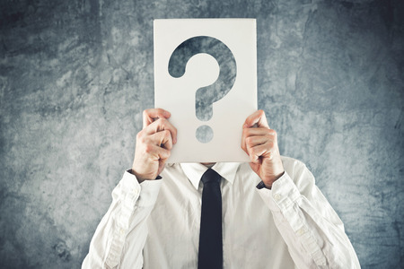 Businessman holding paper with printed question mark in front of his face photo