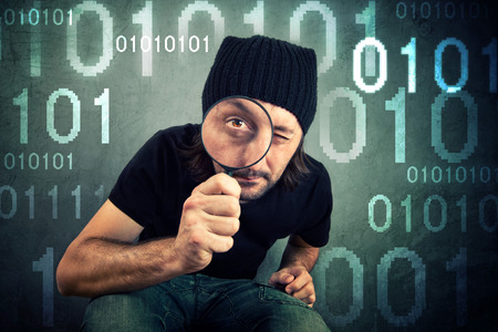 coder: Man looking through magnifying glass and inspecting binary code