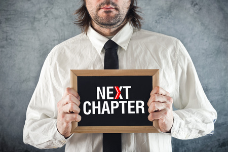 propel: Businessman holding blackboard with NEXT CHAPTER title. Advance in business. Stock Photo