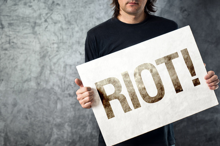 anarchism: Man holding banner with RIOT  printed protest message. Stock Photo