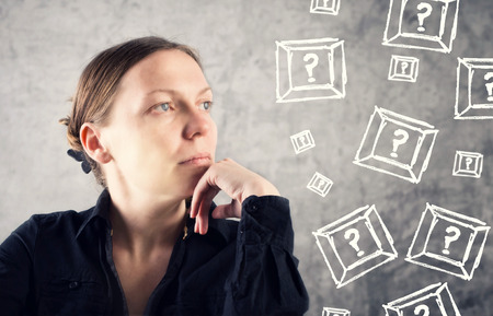 introspection: Portrait of beautiful woman questioning with question marks around her Stock Photo