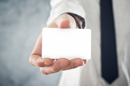 affinity: Businessman holding blank visiting card with rounded corners. Selective focus. Blank  card with copy space for any title or design. Stock Photo