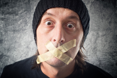 speechless: My lips are sealed. Casual Man with black cap having tape over his mouth. Stock Photo