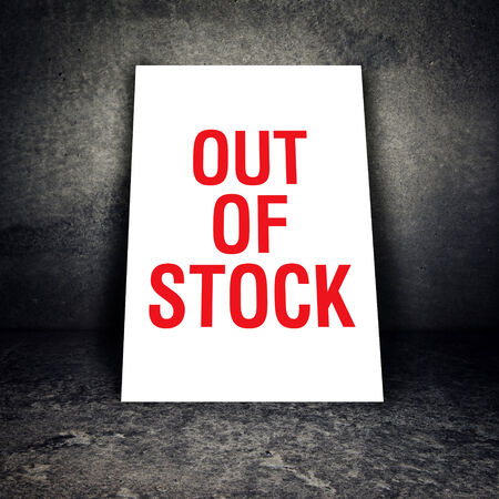 paucity: Out of stock sign leaning on concrete wall of empty warehouse Stock Photo