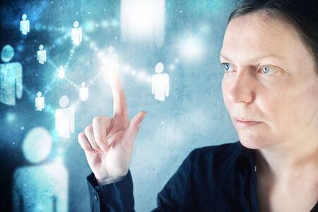 Businesswoman pressing display button on social networking scheme. photo