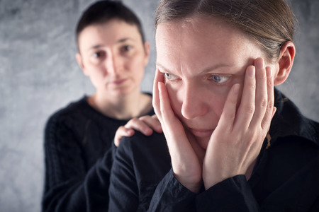 solace: Comforting friend. Woman consoling her sad friend with hand on shoulder.