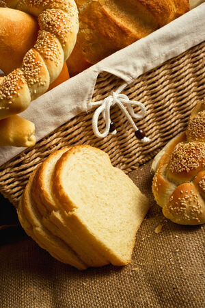 Delicious bread and rolls inwicker basket on kitchen table