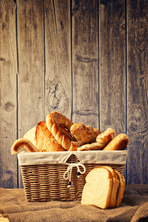 breadloaf: Delicious bread and rolls inwicker basket on kitchen table