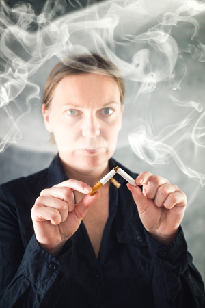 quiting: Woman quits smoking and breaking cigarette in half. healthy lifestyle concept.
