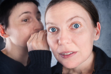 hearsay: Two women gossiping, telling secrets or hearsay stories to one another.