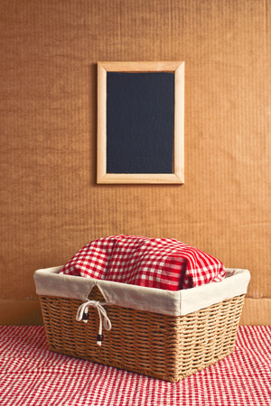 Bread in wicker basket covered with rag on kitchen table with copy space