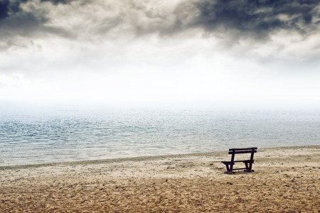 vastness: Empty wooden bench on the beach in cloudy weather. Concept of loneliness, emptiness, solitude.