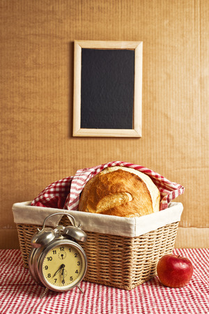 Delicious bread and rolls in wicker basket on kitchen table. Time for breakfast.