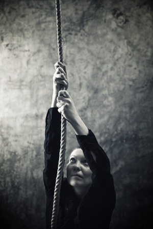 Woman climbing up with rope. Overcaming problems, obstacles and difficulties in life metaphor.