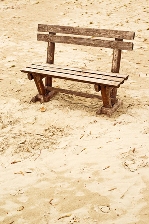 emptiness: Empty wooden bench on the beach in cloudy weather. Concept of loneliness, emptiness, solitude.