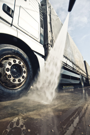 Washing truck service. Commercial transportation vehicle being cleaned.