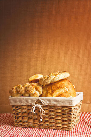 Delicious bread and rolls in wicker basket on kitchen table with copy space