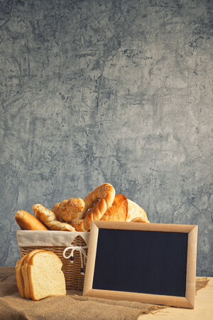 Delicious bread and rolls in wicker basket on kitchen table with copy space.