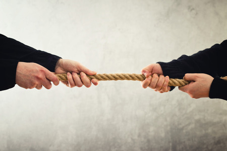 tug o war: Tira y afloja. Mujeres manos tirando de la cuerda hacia lados opuestos. Rivalidad concepto.