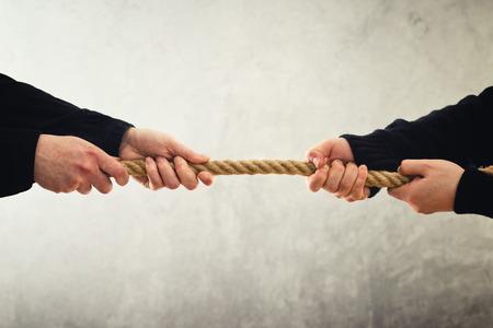tug: Tiro alla fune. Mani femminili che tirano la corda ai lati opposti. Concetto di rivalit�. Archivio Fotografico