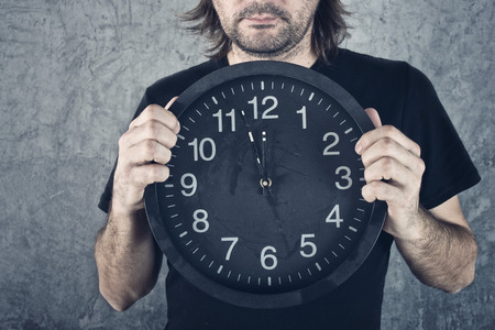 span: Man holding big black clock, two minutes to midnight. Stock Photo
