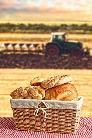 haciendo pan: Pan en cesta de mimbre con tractor y campo agr�cola en el fondo de pan de la imagen conceptual Hacer Foto de archivo