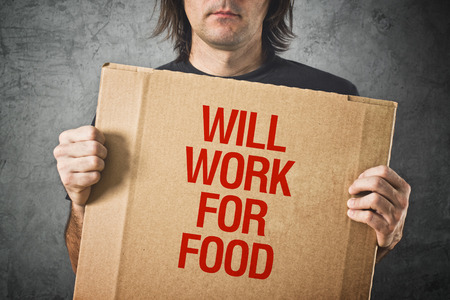bad times: Man needs a job. Unemployed man holding board with title WILL WORK FOR FOOD