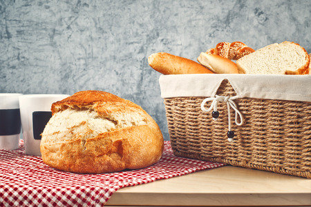 breadloaf: Delicious bread and rolls in wicker basket on kitchen table with copy space