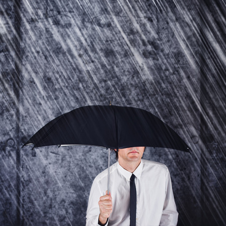 hard times: Businessman with black umbrella protecting from the rain. Business concept for protection, safety, security in hard times of economic depression. Stock Photo