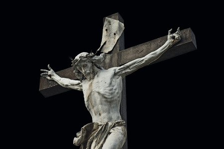 Crucifixion. Christian cross with Jesus Christ statue isolated on black background with clipping work path. Religion and spirituality concept. photo