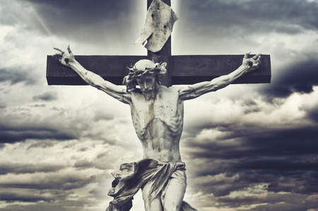 crucify: Crucifixion. Christian cross with Jesus Christ statue over stormy clouds. religion and spirituality concept.