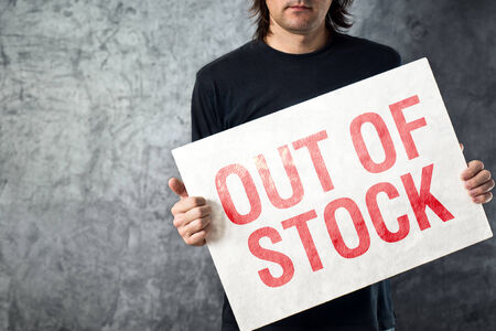 shortage: Out of Stock sign in hands of storage employee, shortage in supply chain