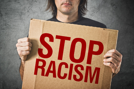 racism: Man holding cardboard banner with STOP RACISM message Stock Photo