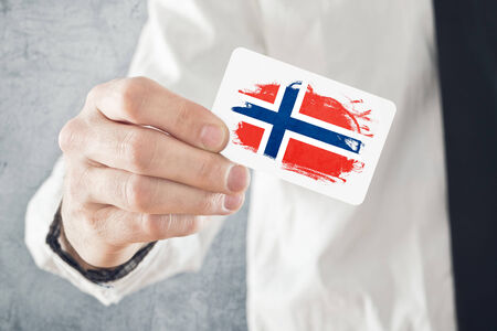 norway flag: Norweigan Businessman holding business card with Norway Flag. International cooperation, investments, business opportunites concept.