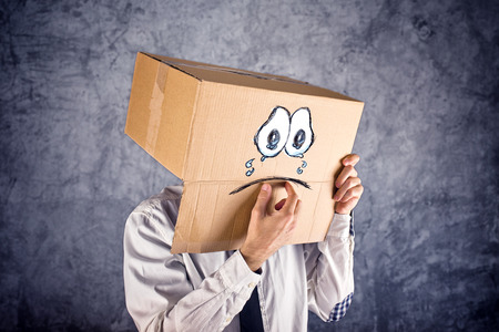 mourn: Businessman with cardboard box on his head and sad crying face expression. Concept of sadness and depression.